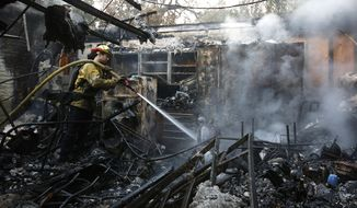 Firefighter Nick Gonzalez-Pomo, of the San Rafael Fire Department, waters down smoldering ashes on a garage Tuesday, Oct. 10, 2017, in Napa, Calif. Wildfires whipped by powerful winds swept through the California wine country sending thousands fleeing as flames rages unchecked through high-end resorts, grocery stores and tree-lined neighborhoods.(AP Photo/Rich Pedroncelli)