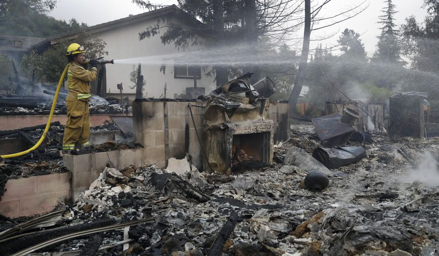 Napa City firefighter Hattie Borg hoses down a fire-ravaged home Monday, Oct. 9, 2017, in Napa, Calif. (AP Photo/Marcio Jose Sanchez)