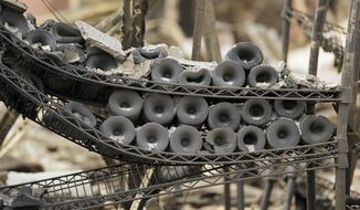 A rack of burned bottles of wine are seen at the Signorello Estate winery Tuesday, Oct. 10, 2017, in Napa, Calif. Worried California vintners surveyed the damage to their vineyards and wineries Tuesday after wildfires swept through several counties whose famous names have become synonymous with fine food and drink. (AP Photo/Eric Risberg)
