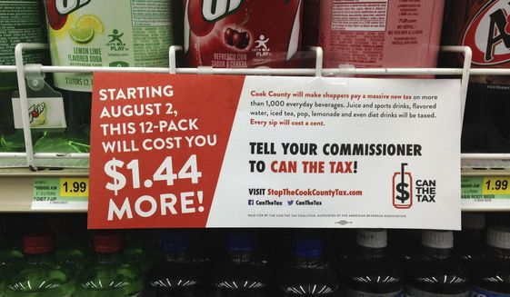 In this on Aug. 22, 2017, file photo, a sign sponsored by opponents of the new Cook County tax on sweetened beverages is posted in the soda isle of Tischler Finer Foods in Brookfield, Ill. (AP Photo by Sara Burnett File)