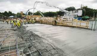 In this Aug. 28, 2017, photo, freshly laid concrete dries on the site of Thor Construction's new north Minneapolis Headquarters. (Evan Frost/Minnesota Public Radio via AP)