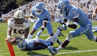 FILE - In this Sept. 30, 2017, file photo, Georgia Tech quarterback TaQuon Marshall (16) dives into the end zone for a touchdown against North Carolina's Dominique Ross (3) and K.J. Sails (9) in the first half of an NCAA college football game in Atlanta. Four games into his Georgia Tech career, Marshall already looks poised to go down as one of the school's greatest quarterbacks. Of course, he'll ultimately be judged on how he perform in games such as Saturday's contest at No. 11 Miami. (AP Photo/John Bazemore, File)