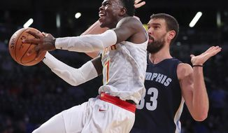 Atlanta Hawks guard Dennis Schroder tries to shoot past Grizzlies Marc Gosol during the second half of an NBA preseason basketball game in Atlanta on Monday, Oct. 9, 2017. (Curtis Compton/Atlanta Journal-Constitution via AP)