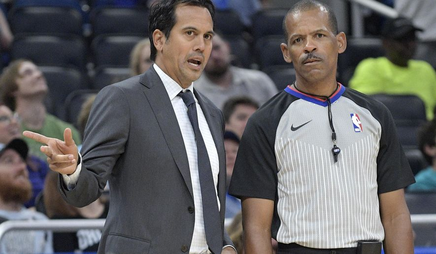 Miami Heat head coach Erik Spoelstra, left, talks to official Eric Lewis on the sideline during the first half of an NBA basketball game against the Orlando Magic Saturday, Oct. 7, 2017, in Orlando, Fla. (AP Photo/Phelan M. Ebenhack)