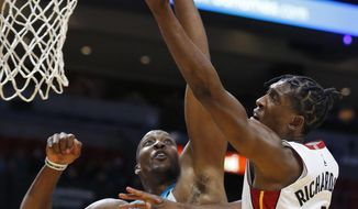 Miami Heat guard Josh Richardson (0) goes up for a shot against Charlotte Hornets center Dwight Howard (12) during the second half of an NBA preseason basketball game, Monday, Oct. 9, 2017, in Miami. The Heat defeated the Hornets 109-106. (AP Photo/Wilfredo Lee)