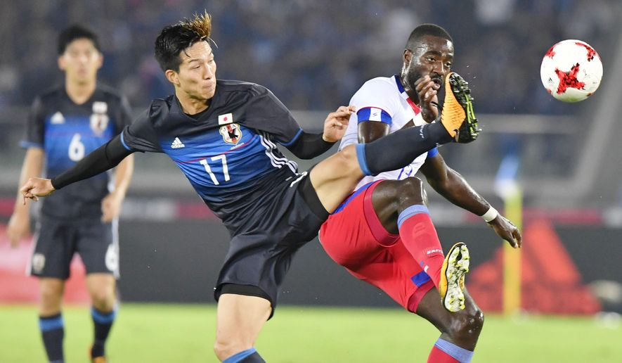 Japan's Yuki Kobayashi, left, and Haiti's Kevin Pierre Lafrance vie for the ball in the first half of their friendly soccer match in Yokohama, near Tokyo Tuesday, Oct. 10, 2017. (Shigeyuki Inakuma/Kyodo News via AP)