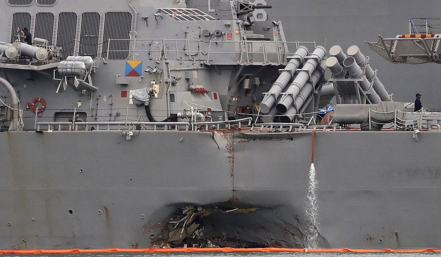 FILE - In this Aug. 22, 2017 file photo, the damaged port aft hull of the USS John S. McCain is visible while docked at Singapore's Changi naval base in Singapore. The U.S. Navy said in a statement Wednesday, Oct. 11, 2017, that the Navy has relieved of duties the commander and executive officer of the USS John S. McCain, which collided with an oil tanker near Singapore in August. (AP Photo/Wong Maye-E, File)