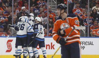 Winnipeg Jets celebrate a goal as Edmonton Oilers' Connor McDavid (7) skates past during second period NHL hockey action in Edmonton, Alberta, on Monday, Oct. 9, 2017. (Jason Franson/The Canadian Press via AP)