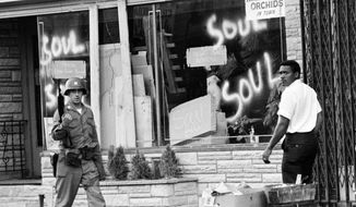 FILE - In this July 15, 1967 file photo a National Guard officer passes the smashed window of a black-owned flower shop in riot-torn Newark, N.J. The last surviving member of the Kerner Commission says he remains haunted that the panel's recommendations on US race relation and poverty were never adopted, but he is hopeful they will be one day. Former U.S. Sen. Fred Harris says 50 years after working on a report to examine the causes of the late 1960s race riots he strongly feels that poverty and structural racism still enflames racial tensions even as the United States becomes more diverse. (AP Photo,File)