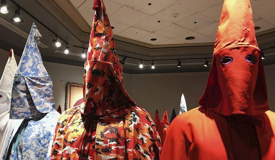 "In this Sept. 21, 2017 file hoto, KKK robes are on display as part of Baltimore artist Paul Rucker's installation entitled ""Rewind"" at York College's Wolf Hall in York, Pa. (Ivey DeJesus/PennLive.com via AP)"