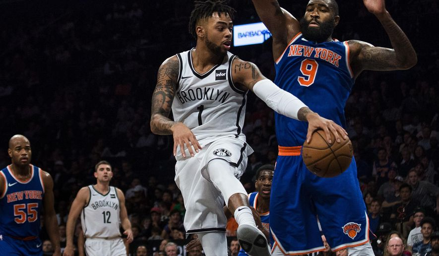 Brooklyn Nets' D' Angelo Russell (1) passes the ball next to New York Knicks' Kyle O'Quinn (9), during the second half of a preseason NBA basketball game, Sunday, Oct. 8, 2017, in New York. (AP Photo/Andres Kudacki)