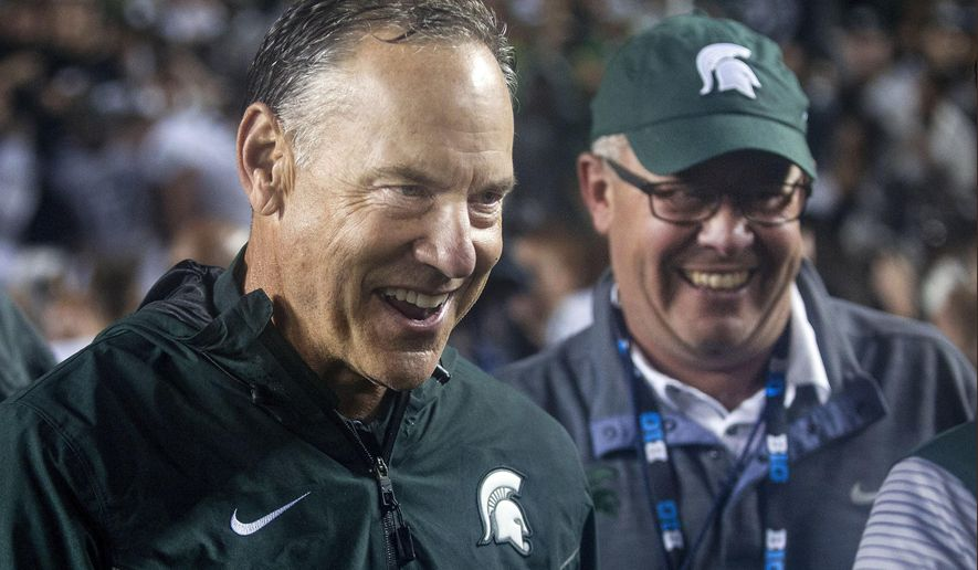 FILE - In this Saturday, Oct. 7, 2017, file photo, Michigan State head coach Mark Dantonio, left, celebrates with athletic director Mark Hollis, right, after the Spartans defeated Michigan 14-10 in an NCAA college football game in Ann Arbor, Mich. Michigan State returned to the Top 25 faster than many people expected. After beating Michigan last weekend, the No. 21 Spartans suddenly have to deal with something that's been mostly absent for the past year, expectations. (AP Photo/Tony Ding, File)