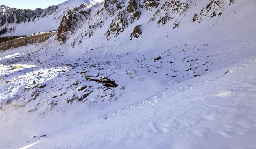 In this Monday, Oct. 9, 2017, photo provided by the The Gallatin National Forest Avalanche Center, a helicopter searches an avalanche debris field for a missing skier on Imp Peak in the southern Madison Range in southwestern Montana. A woman's body was recovered after two skiers triggered the weekend avalanche that fully buried the woman and partially buried a man. (The Gallatin National Forest Avalanche Center via AP)