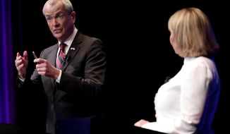 Democratic nominee Phil Murphy, left, answers a question as Republican nominee Lt. Gov. Kim Guadagno, right, listens during a gubernatorial debate at the New Jersey Performing Arts Center, Tuesday, Oct. 10, 2017, in Newark, N.J. (AP Photo/Julio Cortez, Pool)