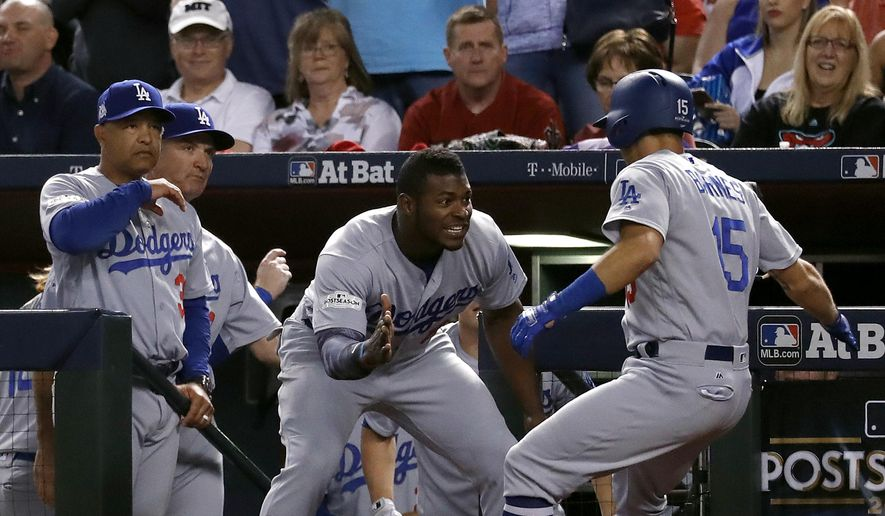 Los Angeles Dodgers' Austin Barnes (15) celebrates with Yasiel Puig in the dugout after hitting a solo home run during the sixth inning of game 3 of baseball's National League Division Series against the Arizona Diamondbacks, Monday, Oct. 9, 2017, in Phoenix. (AP Photo/Rick Scuteri)