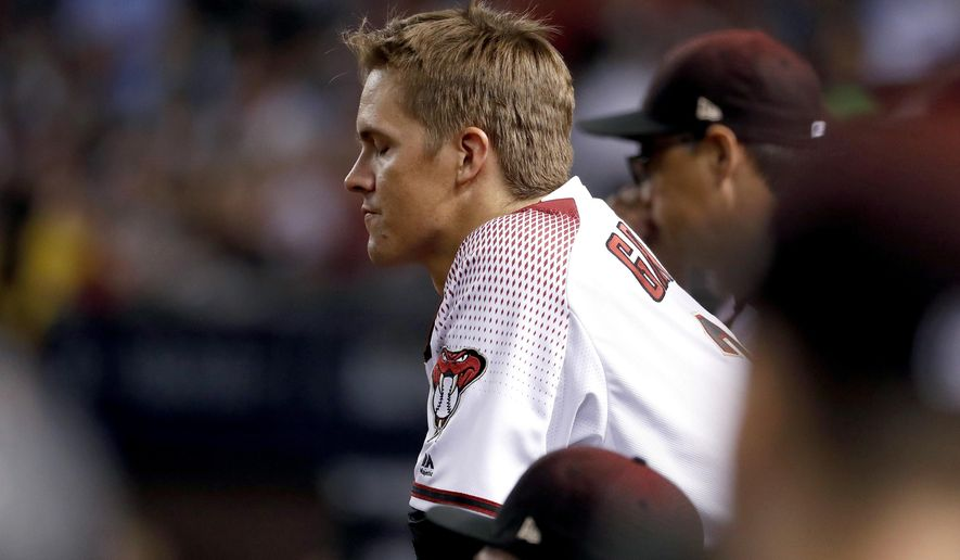 Arizona Diamondbacks starting pitcher Zack Greinke (21) watches from the dugout after being pulled from the game during the sixth inning of game 3 of baseball's National League Division Series against the Los Angeles Dodgers, Monday, Oct. 9, 2017, in Phoenix. (AP Photo/Rick Scuteri)