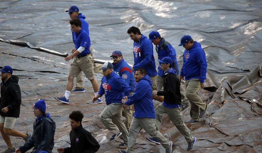 Ground crew cover the infield before Game 4 of baseball's National League Division Series between the Chicago Cubs and the Washington Nationals, Tuesday, Oct. 10, 2017, in Chicago. (AP Photo/Charles Rex Arbogast)