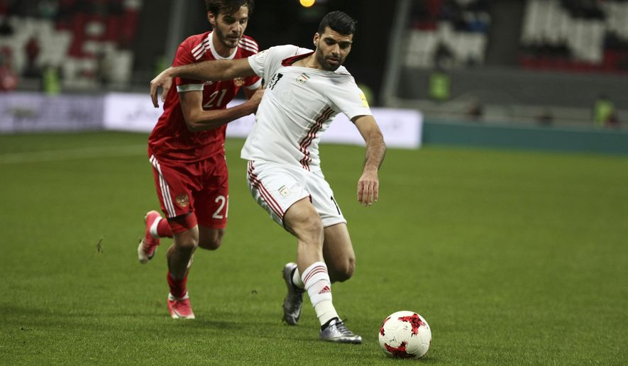 Iran's Akhmad Alenemeh, right, and Russia's Alexander Erokhin vie for the ball, during the friendly soccer match between Russia and Iran, in Kazan, Russia, Tuesday, Oct. 10, 2017. (AP Photo/Nikolay Alexandrov)