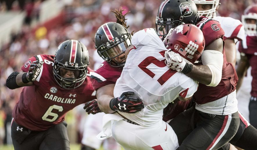 FILE - In this Oct. 7, 2017, file photo, Arkansas running back Devwah Whaley (21) is tackled by South Carolina linebacker Skai Moore (10), Dante Sawyer, center, and T.J. Brunson (6) during the first half of an NCAA college football game, in Columbia, S.C. South Carolina's defense turned a tight game into a blowout with three second-half scores. It's the latest evidence of a defensive turnaround for the Gamecocks and coach Will Muschamp after a struggling debut a season ago. (AP Photo/Sean Rayford, File)