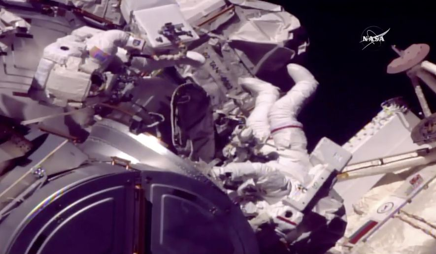 In this frame from NASA TV, Astronauts Mark Vande Hei and Randy Bresnik, right, emerge from the International Space Station on Tuesday, Oct. 10, 2017. The astronauts went out on a spacewalk to grease the robot arm's new hand. (NASA TV via AP)