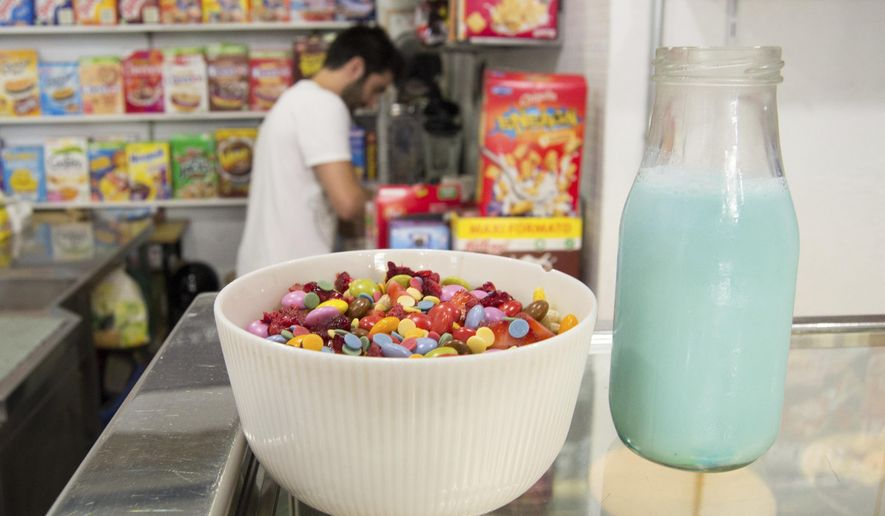 This photo taken Aug. 11, 2017, shows one of the fruity combinations of sugary cereals, topped with candy, at the El Flako cereal cafe in Barcelona, Spain. Behind it is Nicolas Castan, one of the owners, making another healthier combination. (Albert Stumm via AP)