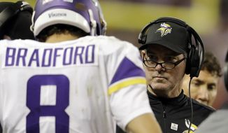 Minnesota Vikings head coach Mike Zimmer talks to quarterback Sam Bradford (8) during the first half of an NFL football game against the Chicago Bears, Monday, Oct. 9, 2017, in Chicago. (AP Photo/Darron Cummings)