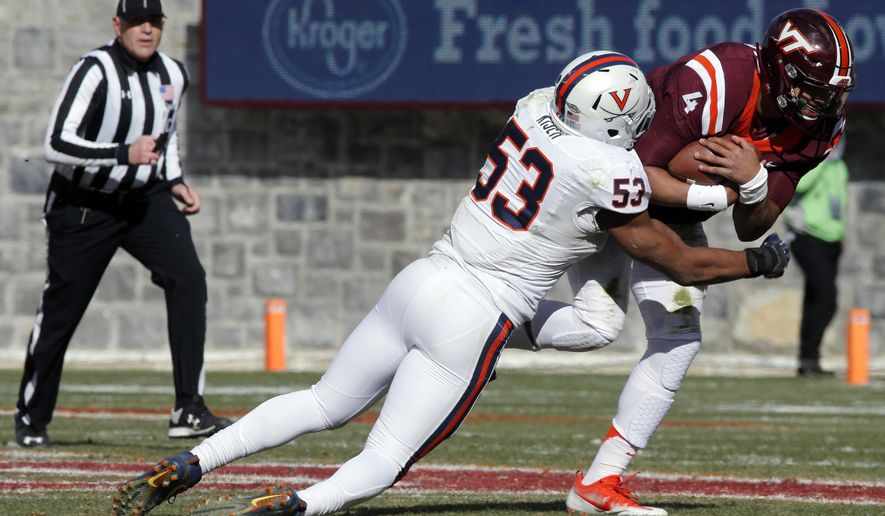 FILE - In this Nov. 26, 2016, file photo, Virginia linebacker Micah Kiser (53) wraps up Virginia Tech quarterback Jerod Evans (4) during the first half of an NCAA college football game in Blacksburg, Va. In Bronco Mendenhall's quest to build a winning football program at Virginia, the biggest assist the coach has received came in the best form possible: buy-in from the players who knew the old way all too well.. (AP Photo/Steve Helber, File)