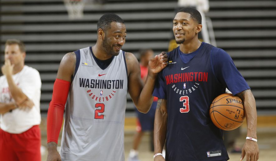 FILE - In this Sept. 28, 2017, file photo, Washington Wizard guards John Wall, (2) and Bradley Beal, (3) share a laugh during practice at NBA basketball training camp in Richmond, Va. The Wizards are sticking with the same group of starters as last season, led by the young core of John Wall, Bradley Beal and Otto Porter Jr., who are all in their 20s and all signed to long-term contracts. Washington will try to make the Eastern Conference finals for the first time in nearly 40 years this season. (AP Photo/Steve Helber, File) **FILE**