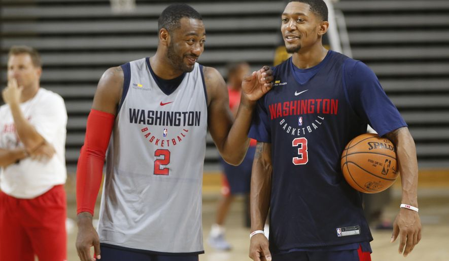 FILE - In this Sept. 28, 2017, file photo, Washington Wizard guards John Wall, (2) and Bradley Beal, (3) share a laugh during practice at NBA basketball training camp in Richmond, Va. The Wizards are sticking with the same group of starters as last season, led by the young core of John Wall, Bradley Beal and Otto Porter Jr., who are all in their 20s and all signed to long-term contracts. Washington will try to make the Eastern Conference finals for the first time in nearly 40 years this season. (AP Photo/Steve Helber, File)