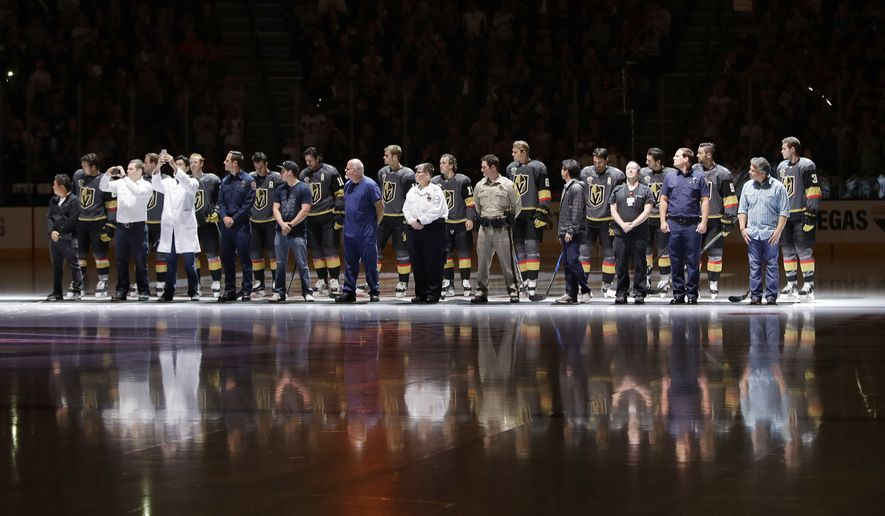 First responders stand with Vegas Golden Knights players during a ceremony to honor the first responders of the shooting in Las Vegas before an NHL hockey game Tuesday, Oct. 10, 2017, in Las Vegas. (AP Photo/John Locher)
