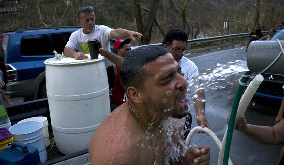 In this Sept. 28, 2017, file photo, people affected by Hurricane Maria bathe in water piped in from a mountain creek, in Naranjito, Puerto Rico. (AP Photo/Ramon Espinosa, File)