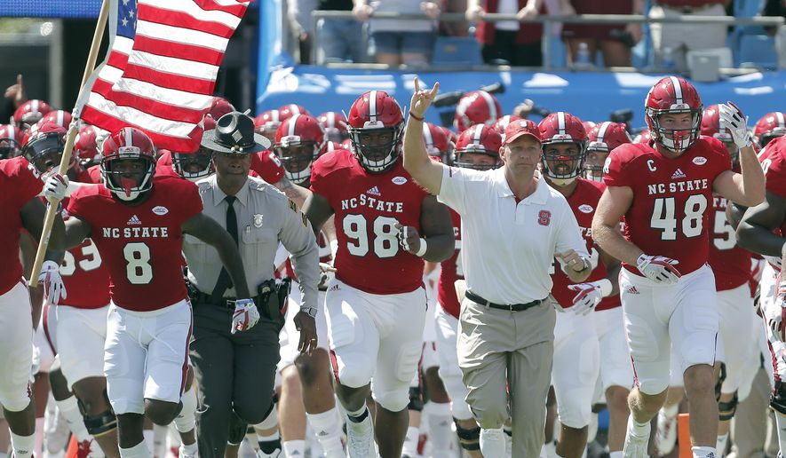 FILE - In this Sept. 2, 2017, file photo, North Carolina State head coach Dave Doeren, second from right, leads his team onto the field for an NCAA college football game against South Carolina in Charlotte, N.C. The ACC seems to be a league with one dominant team in the Clemson Tigers and several solid squads still learning how to contend on the national stage. The Wolfpack is off to their best start since Philip Rivers was the quarterback 15 years ago.(AP Photo/Bob Leverone, File)