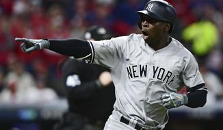 New York Yankees' Didi Gregorius points to the dugout after hitting a two-run home run off Cleveland Indians starting pitcher Corey Kluber during the third inning of Game 5 of a baseball American League Division Series, Wednesday, Oct. 11, 2017, in Cleveland. (AP Photo/David Dermer)