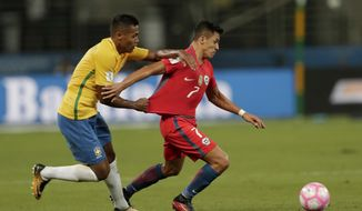 Chile's Alexis Sanchez, right, is held back by Brazil's Alex Sandro during a 2018 World Cup qualifying soccer match in Sao Paulo, Brazil, Tuesday, Oct. 10, 2017. (AP Photo/Andre Penner)