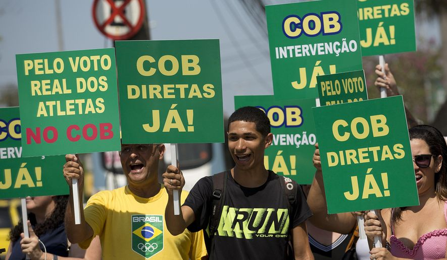 "People protest holding signs with the message that reads in Portuguese: ""COB, Elections now!,"" outside the headquarters of the COB, or Brazil Olympic Committee, in Rio de Janeiro, Brazil, Wednesday, Oct. 11, 2017. The COB called an extraordinary session where it is expected to discuss the arrest of its former president Carlos Nuzman, who was arrested last week in an investigation into a vote-buying scheme to win the rights to host the 2016 Olympics. (AP Photo/Silvia Izquierdo)"