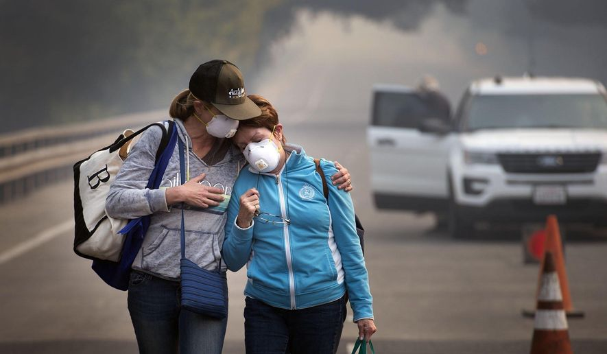 Colby Clark of San Francisco, left, comforts her mother, Bonnie Trexler, after being escorted by law enforcement to her home in Silverado Highland to retrieve medicine and some personal items on Wednesday, Oct., 11, 2017, in Napa, Calif. Trexler was one of the lucky few who found that her home was spared from the devastating fire which burned homes around her Monday. (Randy Pench/The Sacramento Bee via AP)