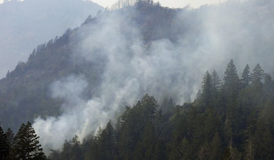 Smoke rises from a wildfire on Wednesday, Oct. 11, 2017 near Calistoga, Calif. The wildfires tearing through California wine country flared anew Wednesday, growing in size and number as authorities issued new evacuation orders and announced that hundreds more homes and businesses had been lost. (AP Photo/Ben Margot)