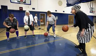 In this Oct. 3, 2017, photo, interim coach Barb Trammell, right, leads fellow players, Debbie Schmitz, from left, Linda Schmitz and Sandy Whiteman in a dribbling drill during a granny basketball team practice at the La Crosse YMCA in La Crosse, Wis. The team for older women started last month. (Peter Thomson/La Crosse Tribune via AP)