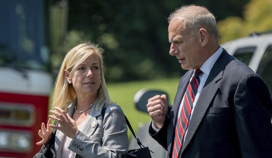 In this Aug. 22, 2017 photo, White House Chief of Staff John Kelly and Deputy Chief of Staff Kirstjen Nielsen speak together as they walk across the South Lawn of the White House in Washington. (AP Photo/Andrew Harnik)