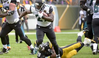 FILE - In this Sunday, Oct. 8, 2017, file photo, Jacksonville Jaguars running back Leonard Fournette (27) breaks a tackle by Pittsburgh Steelers strong safety Sean Davis (28) in the first quarter of an NFL football game in Pittsburgh. Fournette is setting the tone for the run-heavy Jacksonville Jaguars.  (AP Photo/Fred Vuich, File)