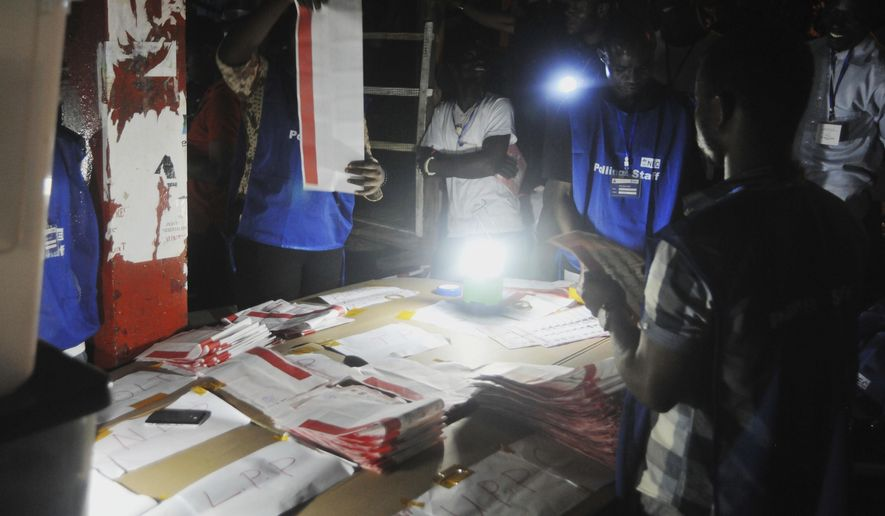 Electoral officials use a lantern as they count ballot papers at the end of voting at a polling station in Monrovia, Liberia, Tuesday Oct. 10, 2017. Polls have closed in Liberia after voters chose between 20 candidates vying to succeed Africa's first female president. When the transfer of power takes place, it will be the first of its kind in the nation in more than 70 years. (AP Photo/Abbas Dulleh)