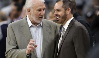 San Antonio Spurs head coach Gregg Popovich, left, and Orlando Magic head coach Frank Vogel, right, visit before a preseason NBA basketball game, Tuesday, Oct. 10, 2017, in San Antonio. (AP Photo/Eric Gay)