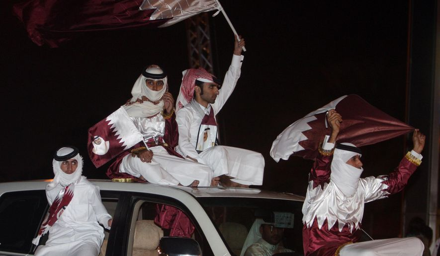 "FILE- In this Friday, Dec. 3, 2010 file photo, Qataris wave the national flag as they celebrate in Doha a day after the world football's governing body FIFA announced that the tiny Gulf state will host the 2022 World Cup. Qatar on Wednesday strongly criticized Emirati officials for questioning Doha's hosting of the 2022 FIFA World Cup, saying that the tournament ""is not up for discussion or negotiation"" amid a diplomatic crisis engulfing the region. (AP Photo/Osama Faisal, File)"