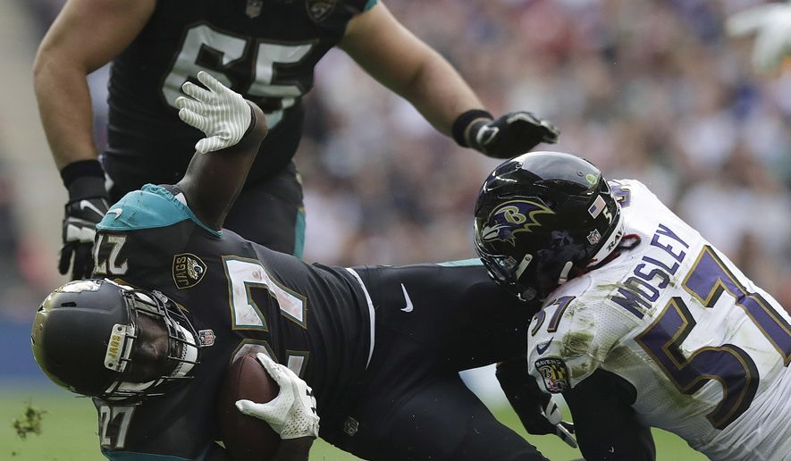 FILE - In this Sept. 24, 2017, file photo, Jacksonville Jaguars running back Leonard Fournette (27) is tackled by Baltimore Ravens inside linebacker C.J. Mosley (57) during the first half of an NFL football game at Wembley Stadium in London. As the man in the middle of the Ravens defense, 2014 first-round draft pick Mosley is the team's leading tackler and already has seven career interceptions. (AP Photo/Matt Dunham, File)