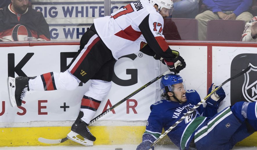 Ottawa Senators' Nate Thompson, left, checks Vancouver Canucks' Michael Del Zotto during the third period of an NHL hockey game in Vancouver, British Columbia, Tuesday, Oct. 10, 2017. The Senators won, 3-2. (Darryl Dyck/The Canadian Press via AP)
