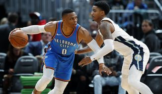 Oklahoma City Thunder guard Russell Westbrook, left, drives to the basket as Denver Nuggets guard Gary Harris defends in the second half of an NBA preseason basketball game Tuesday, Oct. 10, 2017, in Denver. The Thunder won 96-86. (AP Photo/David Zalubowski)