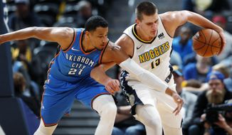 Oklahoma City Thunder guard Andre Roberson, left, battles for control of a loose ball with Denver Nuggets center Nikola Jokic, of Serbia, in the second half of an NBA preseason basketball game Tuesday, Oct. 10, 2017, in Denver. The Thunder won 96-86. (AP Photo/David Zalubowski)