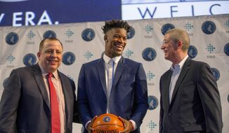 FILE - In this June 29, 2017, file photo, Minnesota Timberwolves new point guard Jimmy Butler, center, is joined by Timberwolves head coach Tom Thibodeau, left, and General Manager Scott Layden during a press conference at Mall of America in Bloomington, Minn. After a disappointing first season in Minnesota, Tom Thibodeau went to some old friends from Chicago for help. Jimmy Butler, Taj Gibson and Aaron Brooks come aboard to help the young Timberwolves get on the same page with their demanding coach. (AP Photo/Andy Clayton-King, File)