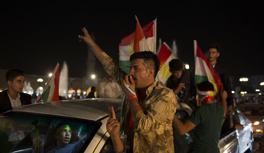 A man with 'yes' shaved into his hair chants through a speaker in the streets of Irbil after polling stations closed on Monday, Sept. 25, 2017. The Kurds of Iraq were voting in a referendum on support for independence that has stirred fears of instability across the region, as the war against the Islamic State group winds down. (AP Photo/Bram Janssen)