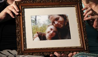 In this June 4, 2014, file photo, mother's Linda Boyle, left and Lyn Coleman hold photo of their married children, Canadian citizen Joshua Boyle and American citizen Caitlan Coleman, who were kidnapped by the Taliban in late 2012, in Stewartstown, Pa. (AP Photo/Bill Gorman, File)